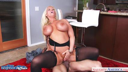 Блондинка в черных чулках и силиконовой грудью занимается сексом на кухне