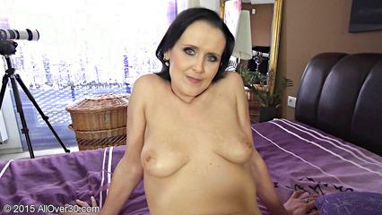 Взрослая брюнетка расположилась на кровати и по мастурбировала