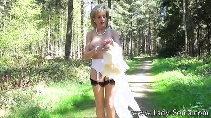 Зрелая обнаженная баба прогуливается по лесу