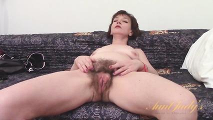 Женщина показывает волосатую пизду перед мастурбацией