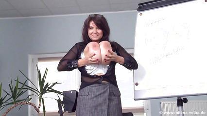 Зрелая брюнетка показывает гигантские дойки во время презентации