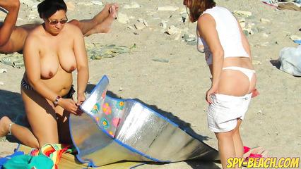 Зрелые бабы не стесняются загорать обнаженными на общественном пляже