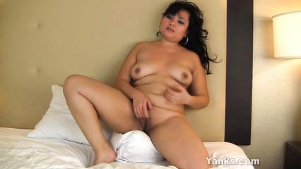 Полненькая азиатка чувственно мастурбирует выбритую пилотку в постели