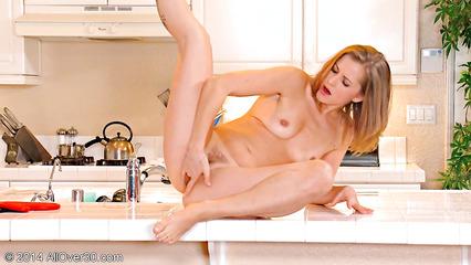 Худенькая блондинка нежно мастурбирует красивую письку на кухонном столе